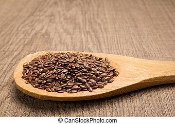 Brown Flax seed. Grains in wooden spoon. Rustic.