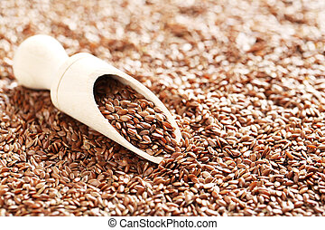Brown flax seeds in wooden scoop
