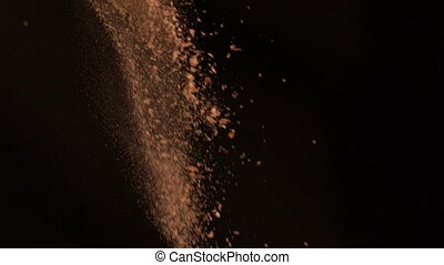 Brown flour falling against black background in slow motion