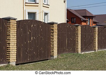 brown gate and fence of wooden planks and bricks in the green grass
