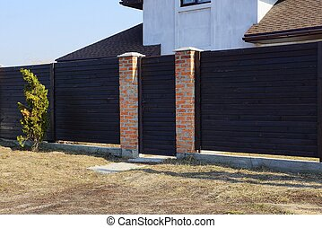 brown gate and wooden fence from the boards in the street