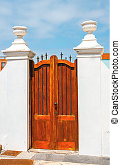 brown gate on a white wall and blue sky in the background