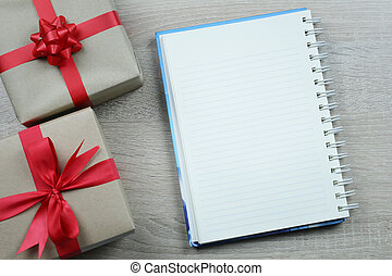 Brown gift box and empty notebook paper for Christmas decoration on wooden floor background.