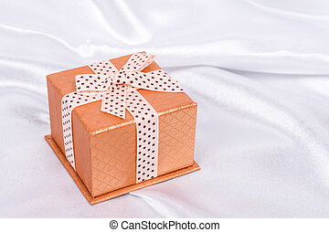 Brown gift box with bow on the white satin background