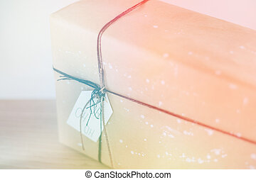 Brown gift box with tag on wooden background. Gift box with red , light toning
