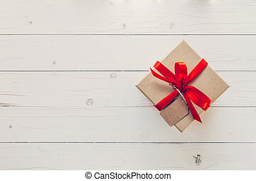 Brown gift box with tag on wooden background. Vintage gift box on wooden background. Gift box with red ribbon on wood background with space.