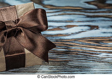 Brown gift box with tied ribbon on wooden background