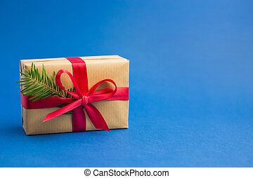 Brown gift boxes with red ribbons and fir tree branch on blue trendy background. Color of the year. Present for Christmas