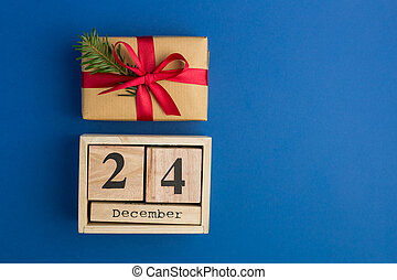Brown gift boxes with red ribbons and fir tree branch on blue trendy background. Festive backdrop for projects. Flat lay style. Top view. Color of the year. Christmas Eve Date On Calendar. December 24