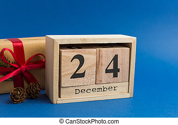 Brown gift boxes with red ribbons and fir tree branch on blue trendy background. Festive backdrop for projects. Color of the year. Christmas Eve Date On Calendar. December 24