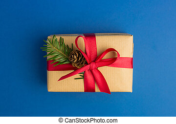 Brown gift boxes with red ribbons and fir tree branch on blue trendy background. Festive backdrop for projects. Flat lay style. Top view. Color of the year. Present for Christmas