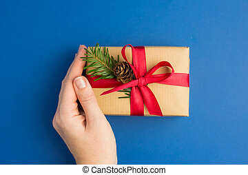 Brown gift boxes with red ribbons and fir tree branch on blue trendy background. Woman hand holding present for Christmas box. Flat lay style. Top view. Color of the year.