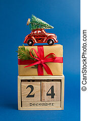 Brown gift boxes with red ribbons and fir tree branch, red toy car and Calendar on blue trendy background. Color of the year. Present for Christmas. December 24