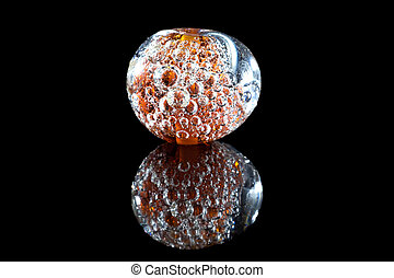 Brown glass bead with bubbles on black background