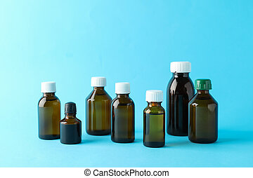 Brown glass medical bottles on blue background, space for text