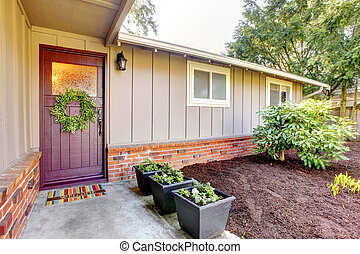 Brown grey house exterior with front door and spring landscape.