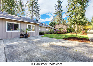 Brown grey house exterior with large driveway.