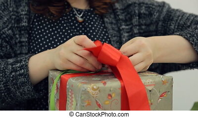 Brown-haired designer ties bow on packing new year present isolated