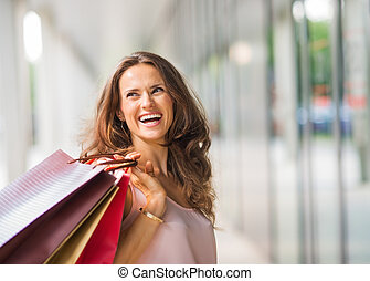 Brown-haired, happy, smiling woman holding up shopping bags
