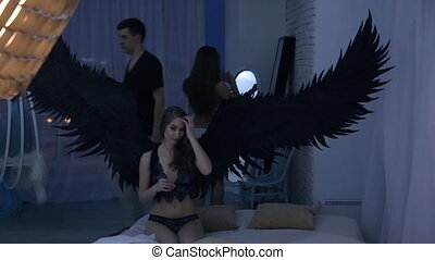 Brown-haired model with angel wings in underwear at photo shoot