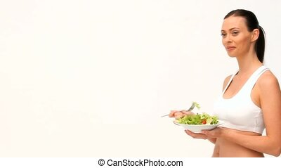 Brown-haired woman eating a salad isolated on a white...
