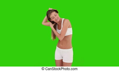 Brown-haired woman is fixing her hair against a green screen