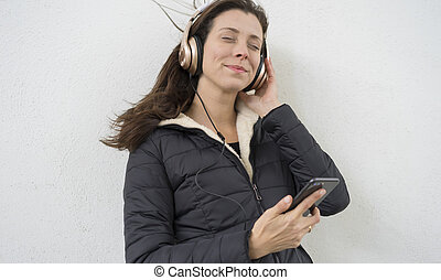 Brown-haired woman listening to music with the mobile. enjoying music with golden and white helmets on the street in winter
