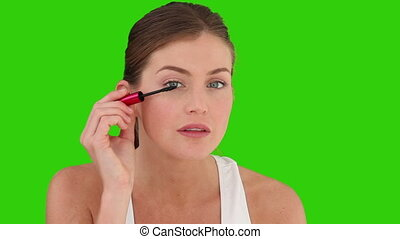 Brown-haired woman putting on make-up