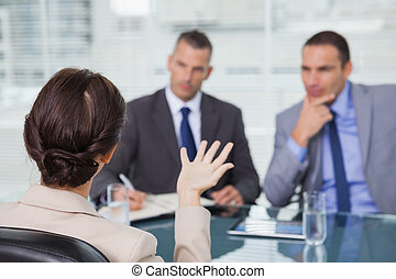 Brown haired woman talking to her interviewers
