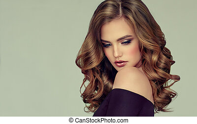 Young brown haired woman with voluminous, shiny and wavy hair . Beautiful model with long, dense and curly hairstyle. Frizzy hair, bright makeup and sincere toothy smile.