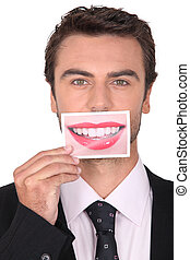brown-haired young man holding picture of female mouth smiling