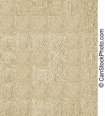 handwritten alphabet letters on sand