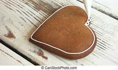 Brown heart shaped cookie. Piping lace on heart-shaped dessert. How to ice biscuits.