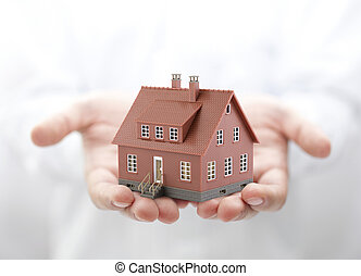 Brown house miniature in hands