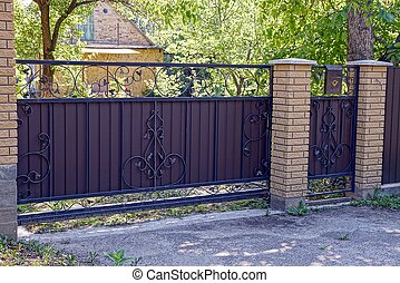 Brown iron gate with a pattern and a brick fence in front of the road