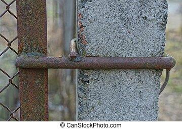 brown iron rusty rod on gray concrete pillar fence wall
