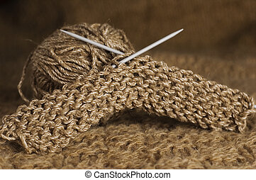 brown knitting and clew on beige background