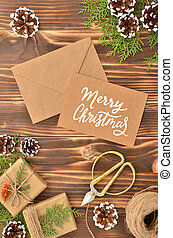Brown kraft envelope with calligraphy handwritten sign Merry Christmas on wooden table with vintage tone. Top view New Year frame with pine cones, gift boxes and fir branches