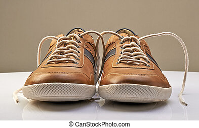 Brown Leather Shoe with white shoelaces open on a white...