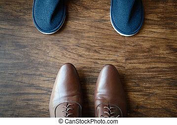 brown leather shoes placing opposite to a blue slippers on a wooden floor texture