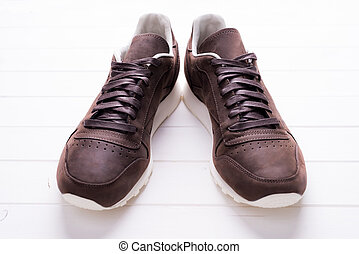 brown leather shoes with laces on wooden background