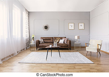 Brown leather sofa in elegant living room interior with stylish armchair, coffee table and drawings on the grey wall