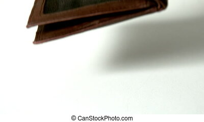 Brown leather wallet falling on white surface in slow motion
