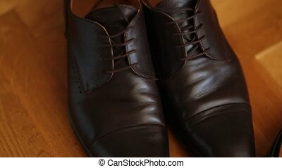 Brown man's shoes with laces on a wooden floor.