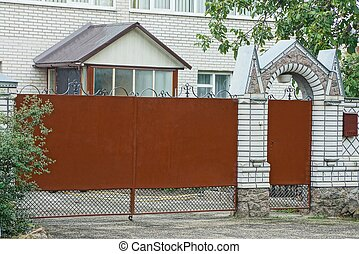 brown metal closed gate and part of a brick fence in the street