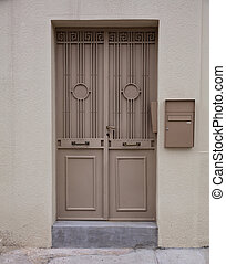 Brown metal entrance door on beige color wall background,...