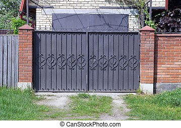 brown metal gate with forged pattern and part of a brick fence outside