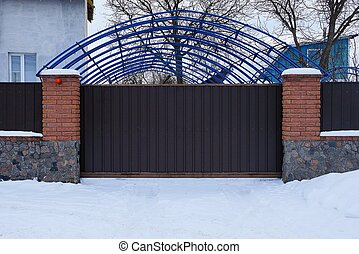 brown metal gates and a brick fence outside in white snow drifts