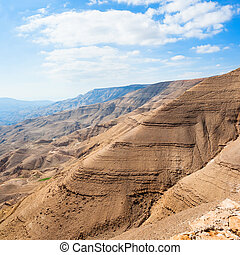 brown mountains in valley of Wadi Mujib river - Travel to...