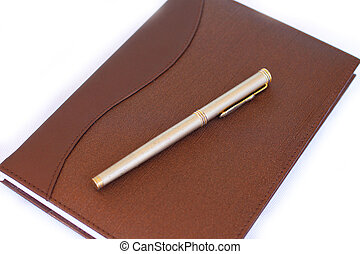 Brown note book and pen